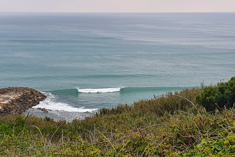 A lefthand wave breaking off the jetty at Papucos just south of Ericeira