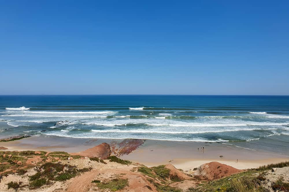 Waves breaking both left and right at the amazing Praia da Almagreira with the red rock formations
