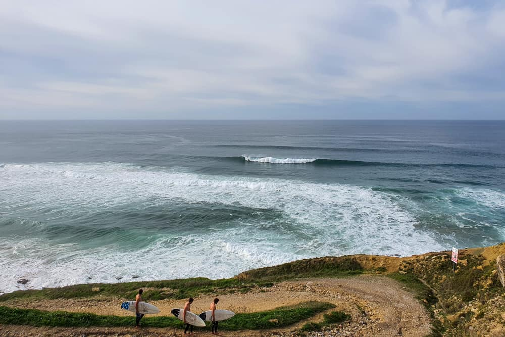 Surfers walking down the dirt road at Praia Pequena in Sintra