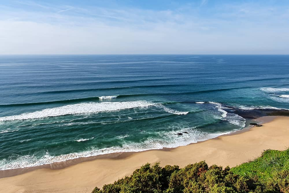 The remote beach of Praia da Vigia with an a-frame wave