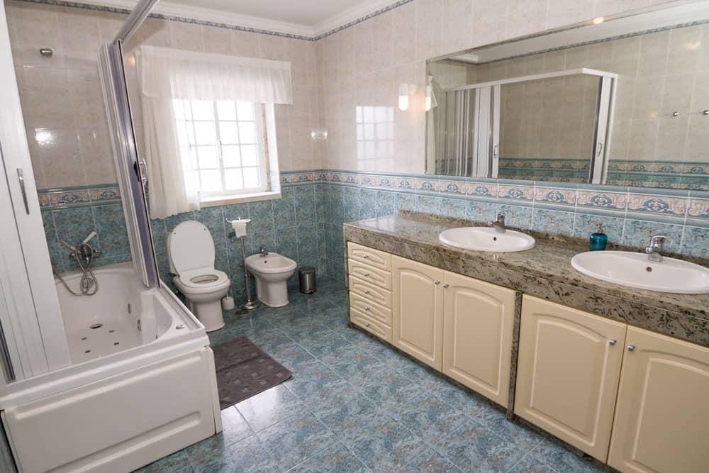 The big bathroom of the family room with bathtub, double washbasin, toilet and bidet
