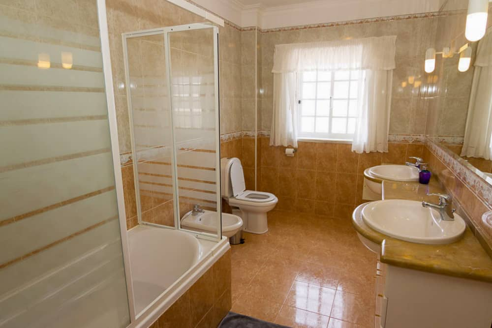 Shared bathroom with shower, double washbasin, toilet and bidet