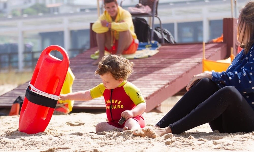 Toddler playing with safety equipment on Foz do Lizandro beach while the family is watching