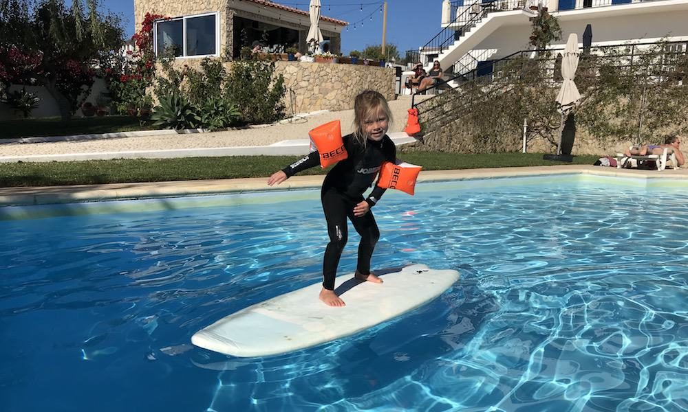 Kid is having fun on a surfboard in the pool while the family is watching