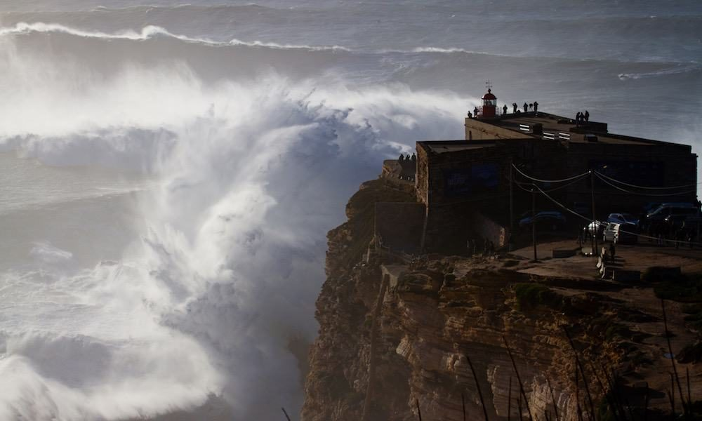 Giant waves breaking in front of the lighthouse in Nazaré