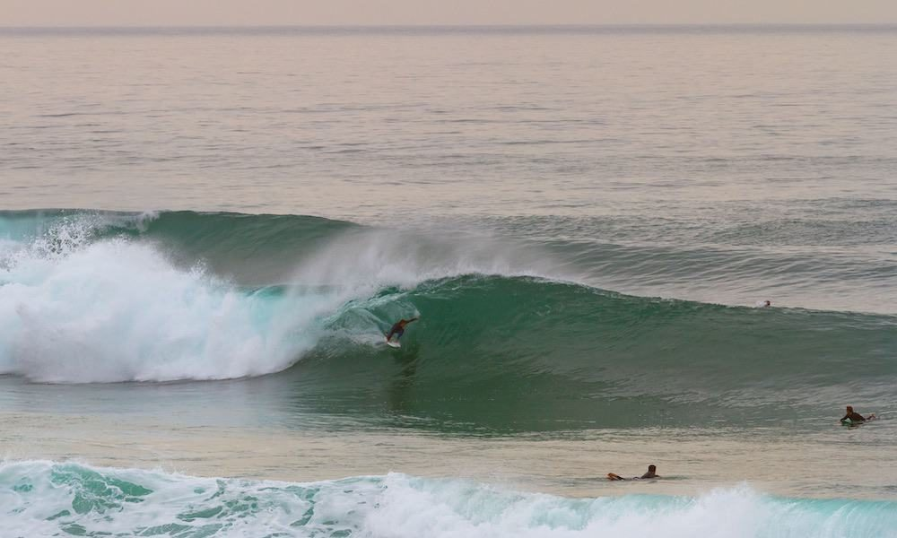 Surfing a perfect lefthand barrel at the surf spot Foz do Lizandro